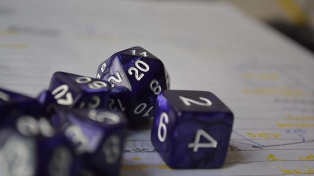 purple polyhedral dice on paper
